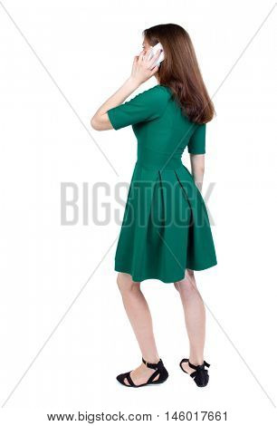side view of a woman walking with a mobile phone. back view of girl in motion. slender brunette in a green short dress stands sideways and and talking on the phone.