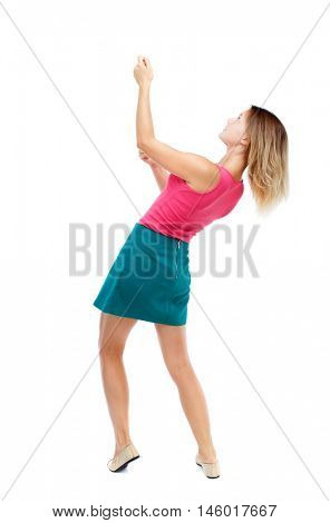 back view of standing girl pulling a rope from the top or cling to something. Isolated over white background. Blonde in a red sweater and green skirt sitting on a rope.