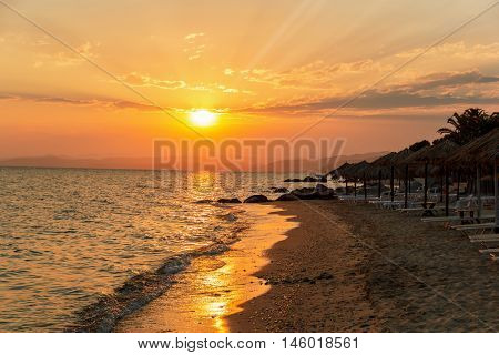 Sun loungers with an umbrella on the beach at sunset