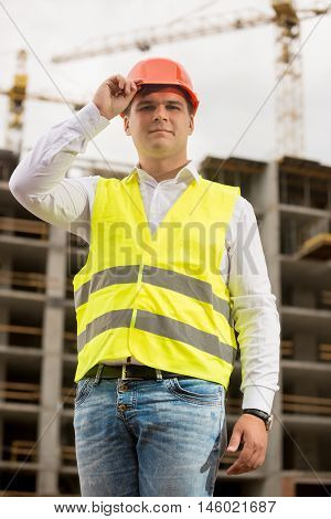 Portrait of handsome smiling engineer in hardhat posing against working construction crane