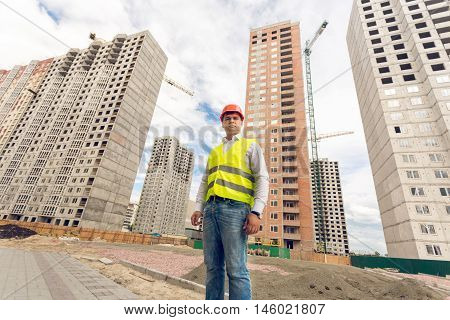 Wide angle portrait of young construction foreman standing on building site
