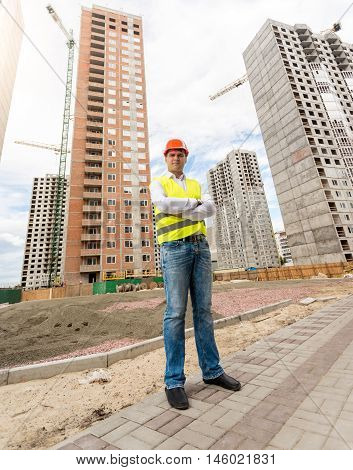 Young construction engineer standing in front of buildings under construction