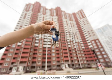 Closeup image of female hand holding keys from new apartment. New big building on the background