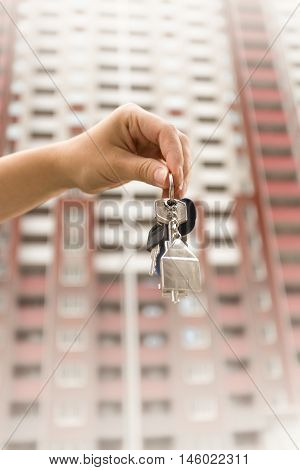 Closeup image of hand holding keys against high new building