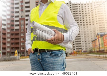 Closeup photo of architect in safety vest posing with blueprints at new buildings