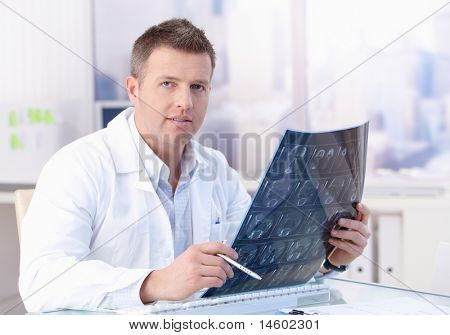 Middle-aged doctor studying x-ray image in office.?
