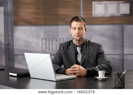Top manager meditating in elegant office, sitting at desk.?