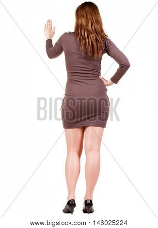 back view of Businesswoman . Young bisiness woman in dress presses down on something. Isolated over white background. Rear view people collection. backside view of person. she holds his hand open