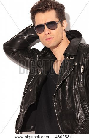 portrait of a cool rocker in leather jacket holding hand behind head on white background