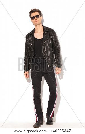 full body picture of an arrogant young fashion man in leather jacket and sunglasses posing on white background