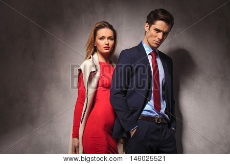 sexy blonde woman in red dress and long coat standing behind her man in suit and tie