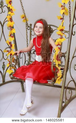 Happy little girl with long brown hair to her waist . Girl in bright red dress. Girl swinging on a swing with his legs