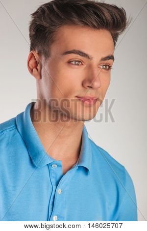 side view of a young man in blue polo shirt looking away from the camera