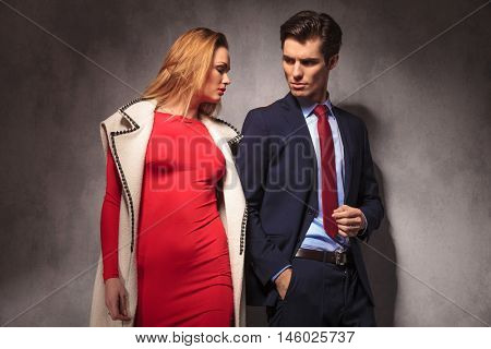dramatic young elegant couple posing together in studio, woman in red dress and long coat, man in suit and tie