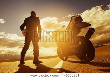 Biker with motorcycle stands on straight road in sunset light