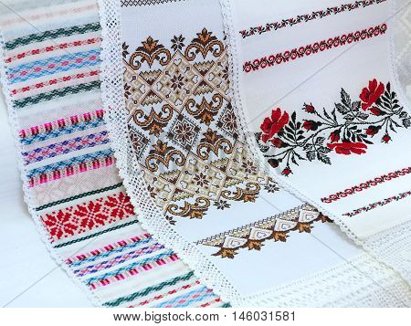 Old traditional balkan handmade floral embroidery on white canvas .