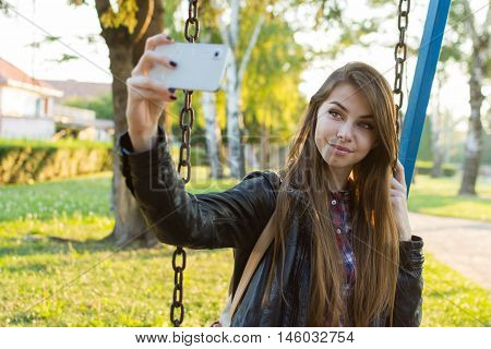 Beautiful blonde Caucasian teenage girl taking a selfie on smart phone in park in autumn. Millennial young woman taking a photo of herself outdoors in fall. No retouch, natural light.