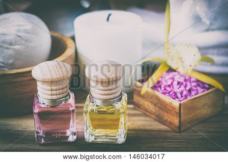 Spa still life of massage oil bottle of aroma essential oil or spa and natural fragrance oil with flower on wooden table Composition of spa treatment on table colorful background.