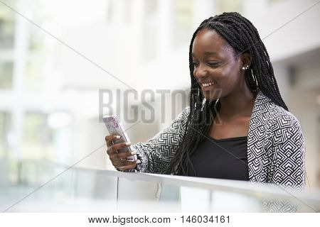 Young black female student using phone in university foyer