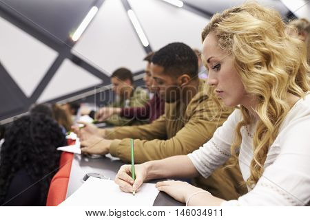 Female student taking notes in a university lecture theatre