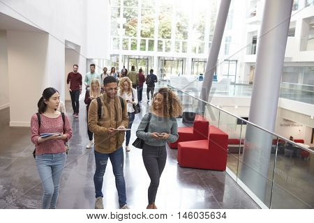 Students walk and talk using mobile devices in university
