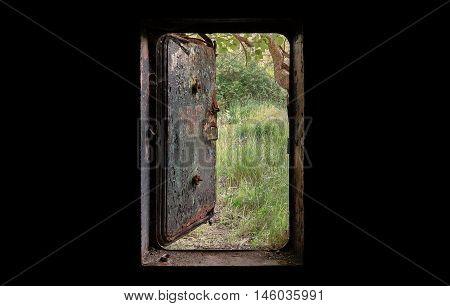 Open the door of the old bunker. The view from the dark nature behind a door.