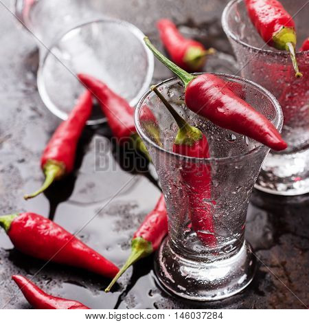 Food and drink, holidays, still life concept. Vodka shot with chili peppers on rusty grunge table. Selective focus