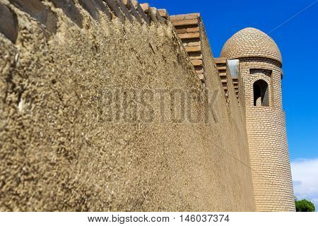 minaret of a mosque and a wall against the blue sky