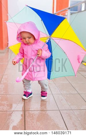 Little girl with colorful umbrella walking in the rain.