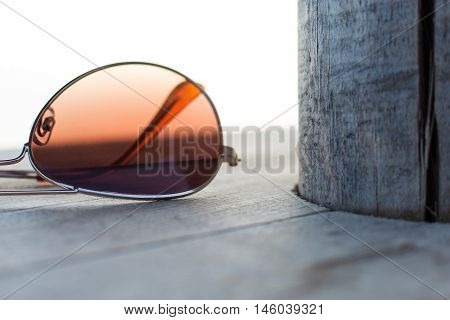 Brown Mirrored Sunglasses Detail on the Wooden Background Close Up and Selective Focus. Fashion Concept.