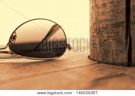 Mirrored Sunglasses Detail on the Wooden Background Close Up and Selective Focus. Fashion Concept in Sepia.
