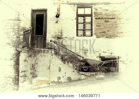 Old Stone House With Wooden Door And Window, Staircase, Rusty Gutter And Wheelbarrow