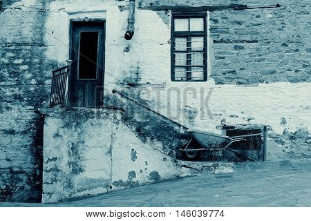 Old Stone House With Wooden Door and Window Staircase Rusty Gutter and Wheelbarrow in Cyan