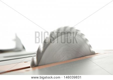 Close-up image of a spinning table saw blade.  On a white background with space above for your text.