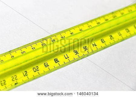 Yellow plastic cleical ruler closeup on a white background.