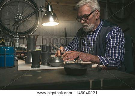 Elderly Man Soldering Metal Rings In Workshop