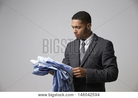 Studio Portrait Of Male Fashion Buyer Looking At Shirts