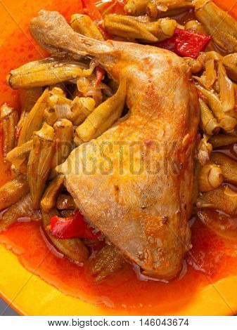Chicken tight with okra. Stewed with tomatoes. Shot from above