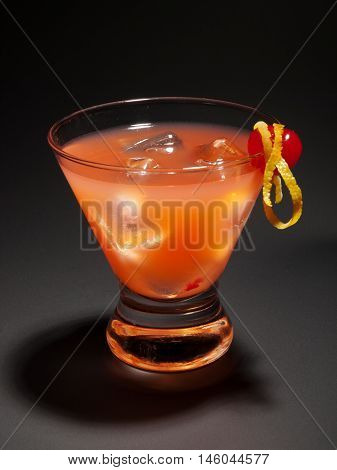 Cocktail with gin vermouth and orange juice isolated on black background