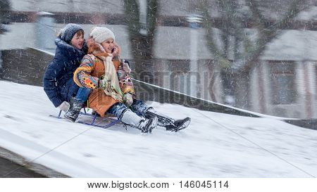 Yuzhnoukrainsk Nikolaev region Ukraine - January 17 2016: Two days had the annual rate of snow wind 15-20 m s with gusts up to 28 m s the school canceled but it is not a barrier for children's fun. Two girls move down from the hill. Winter, blizzard, fros