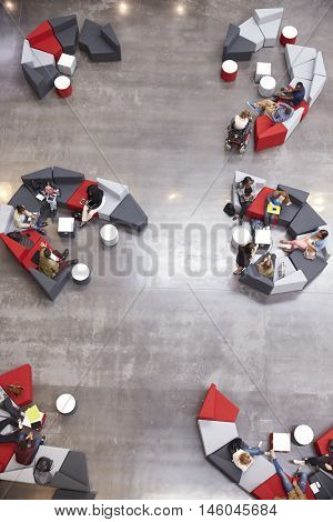 Students groups sit in a modern university atrium, vertical