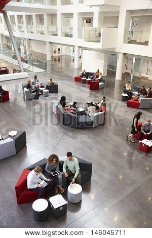 Students sitting in university atrium, vertical