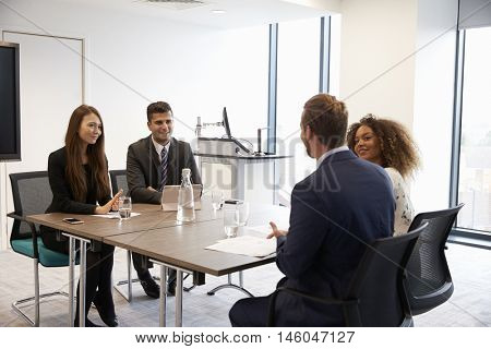 Businesspeople Working Together At Desk In Modern Office