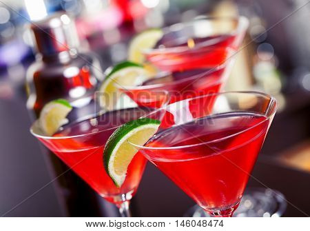 Cosmopolitan cocktails shot on a bar counter in a nightclub. High angle tilted