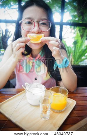 portrait of happy asian woman in a cafe with orange fruite against of a mouth like a smile ,say cheese concept,happy with food concept,happy morning breakfast