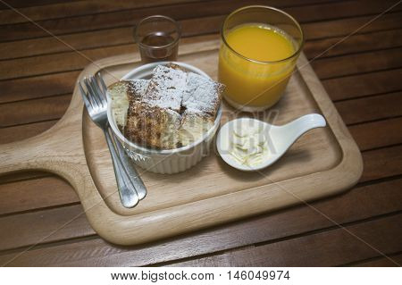 close up toast in a cup with icing sugar powdered on top, honey in a mug shot and orange juice in a glass, put on wooden plate wooden table ,morning breakfast,honey toast menu