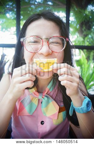 portrait of happy asian woman in a cafe with orange fruite against of a mouth like a smile,say cheese concept,happy with food concept,happy morning breakfast