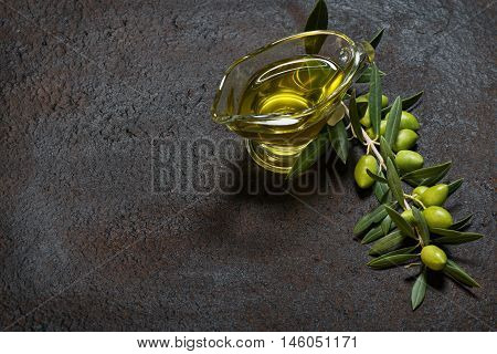 Twig with green olives and glass sauceboat of olive oil on a black old metal background.
