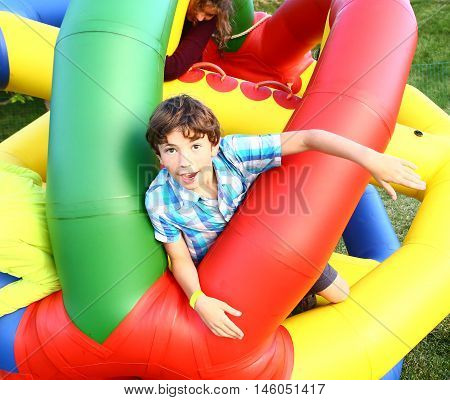 preteen happy boy in outdoor amusement park attraction inflated ball close up laughing portrait