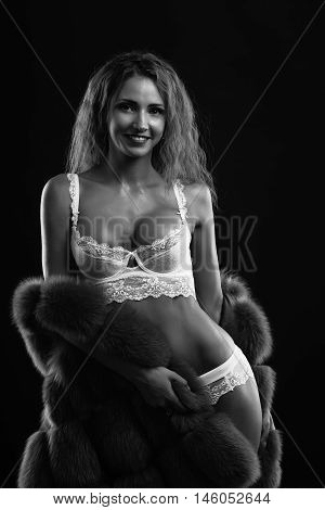 Woman in lingerie posing on a dark background in the studio. Black and white photo.